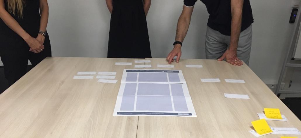 Des participants découvrent le contenu à placer sur un écran papier, lors d'un atelier UX
